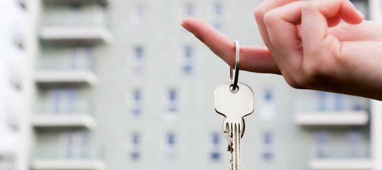 A real estate agent holding keys to a new apartment in her hands. Real estate industry