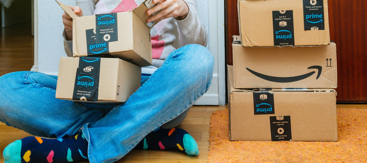 Woman sitting on ground opening Amazon packages