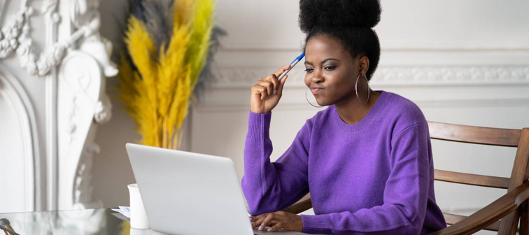 Black millennial woman employee working on laptop and feeling visibly annoyed.