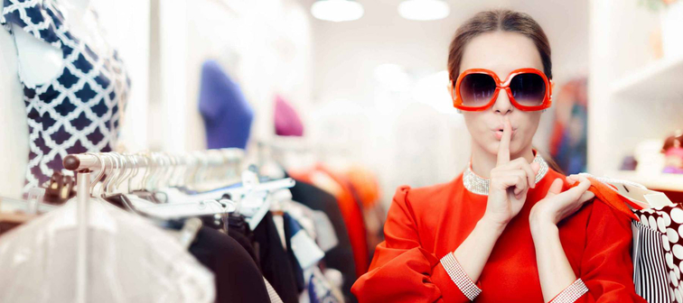 Woman with finger over her lips, wearing sunglasses in a clothing store