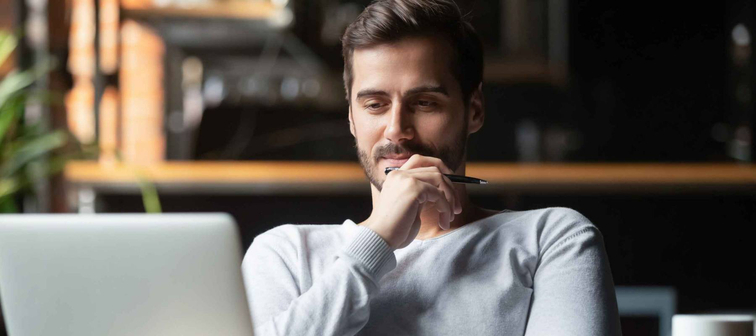 Thoughtful investor thinks while looking at laptop at workplace, dreamy professional consider solution sit at work desk with computer, student search new idea inspiration in office cafe