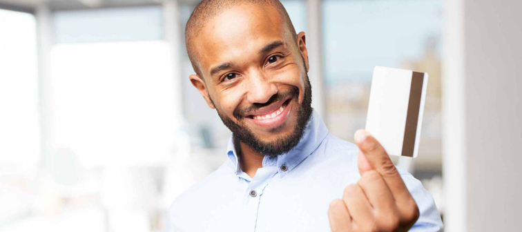 Man smiles with credit card
